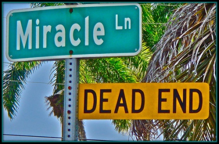 Miracle Ln. street sign and a dead end street sign